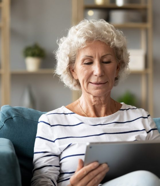 Mature woman using tablet for virtual telehealth psychology.